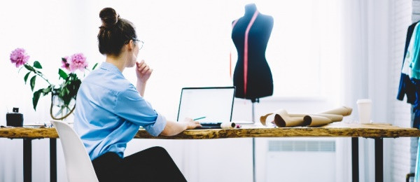 Room with fashion tools and girl sitting at writng desk with laptop